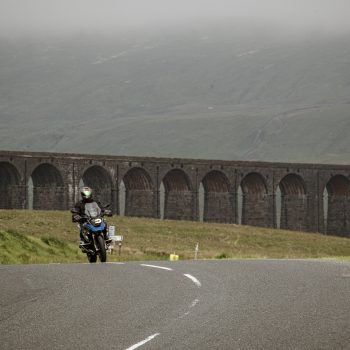 A motorcyclist riding near the Ribblehead Viaduct in Yorkshire.
