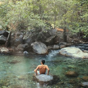 Marcos, hospitality professional, sitting in the water at San Gabriel, California.