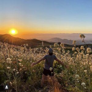 Marcos standing in a field of flowers at Sandstone Peak Valley in Malibu, Hawaii.