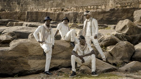 Songhoy Blues in white posing on some rocks.
