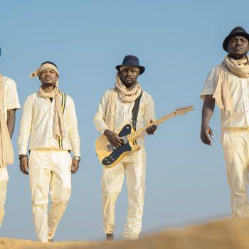 Songhoy Blues in white walking over the desert