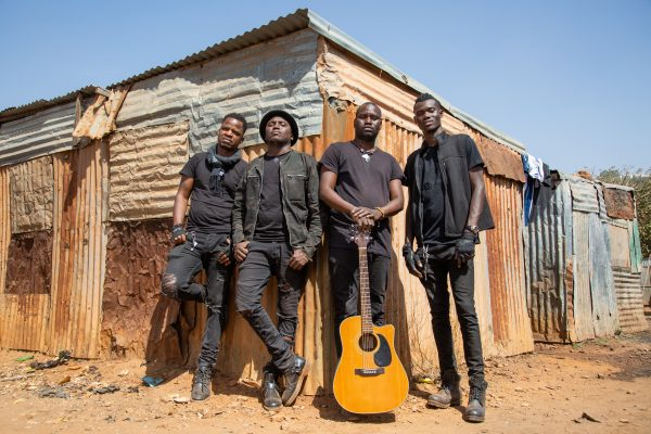 Songhoy Blues with guitar in front of building
