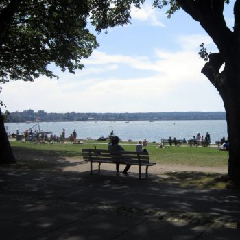A photo of the water in Stanley Park from behind a shaded bench near Vancouver.