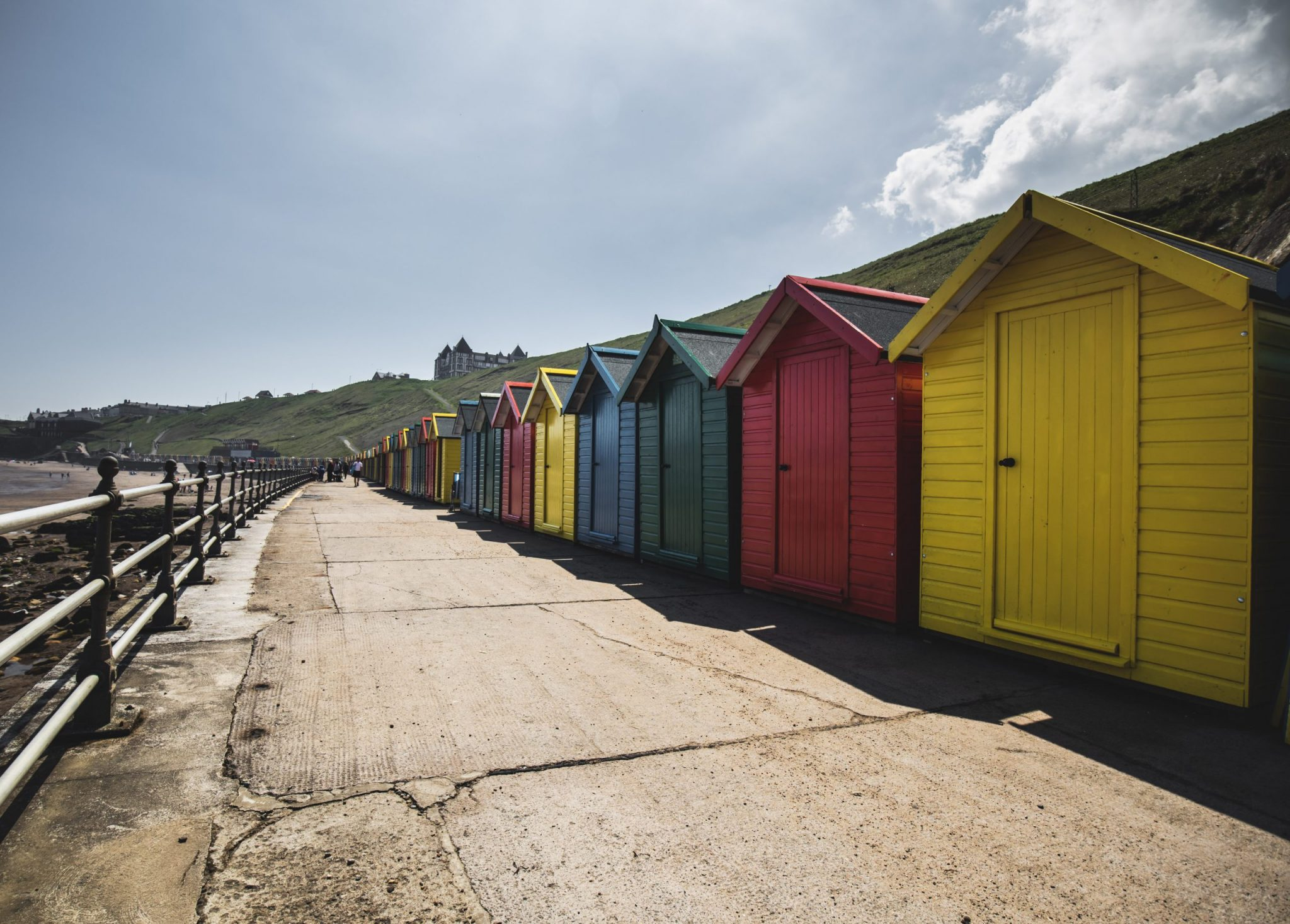Whitby beach huts in the sunshine in Yorkshire.