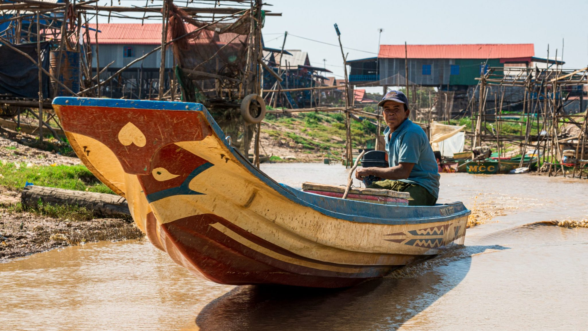 A photo of a villager rowing a canoe in Kompong Phluk, Cambodia.