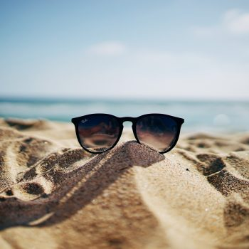 Sunglasses propped up in the sand on a beach