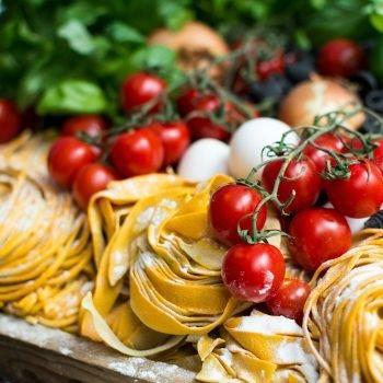 A photo of homemade pasta, mozzarella, and tomatoes