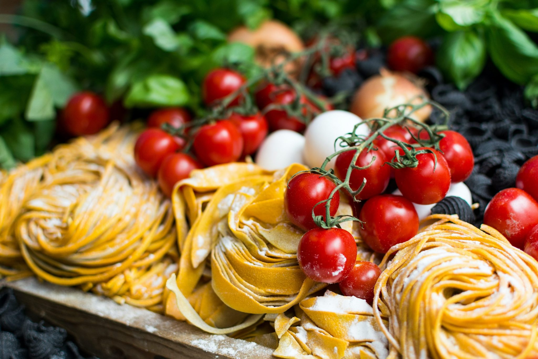 A photo of homemade pasta, mozzarella, and tomatoes