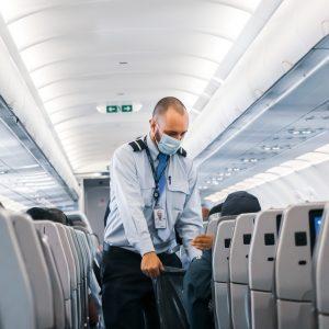 A flight attendant wearing a mask.