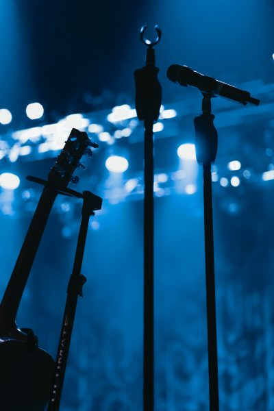 Microphone stands and a guitar on a blue stage