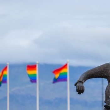 Violinist statue with pride flags