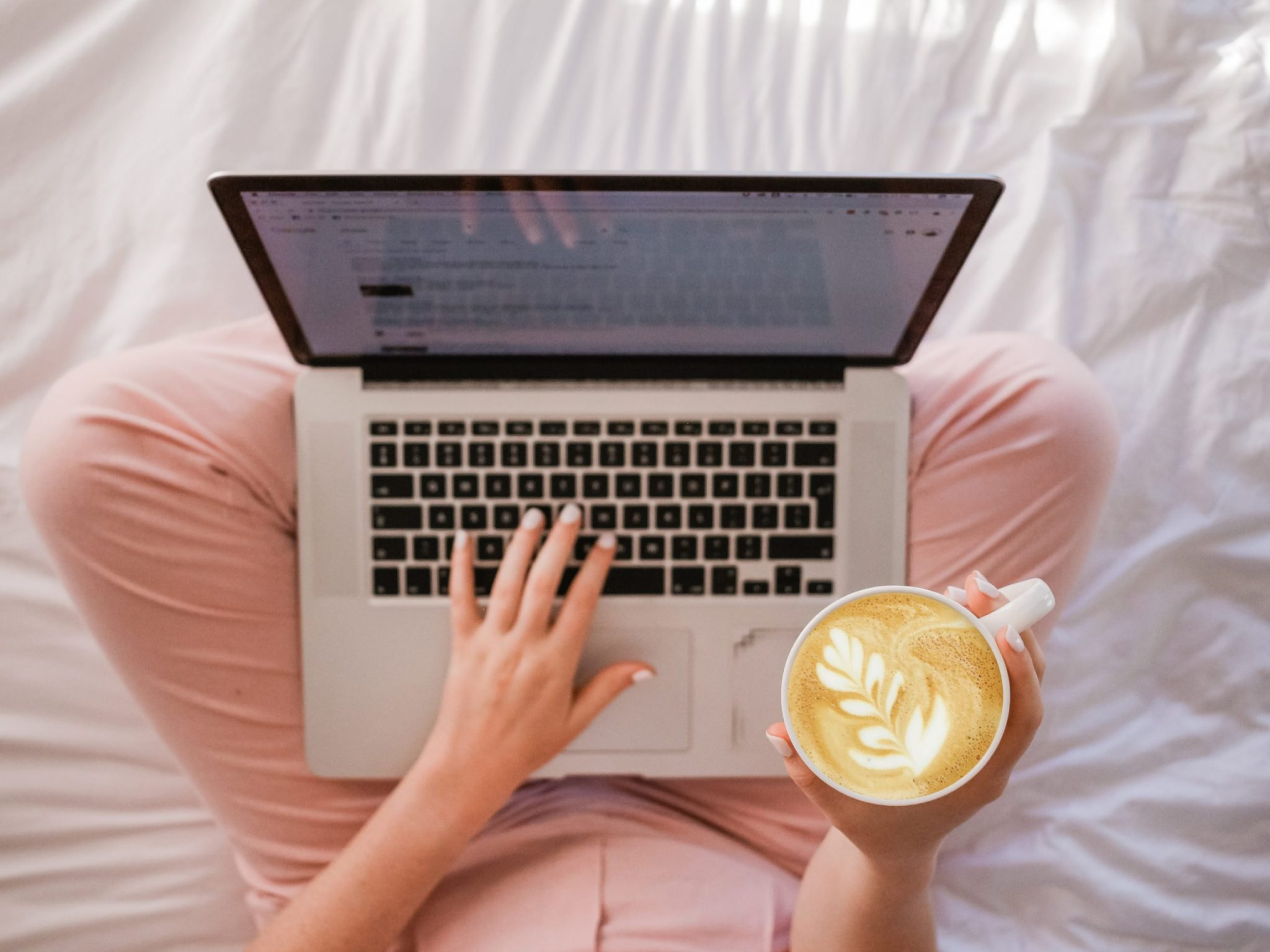Phooto of woman holding coffee and working on a laptop in bed
