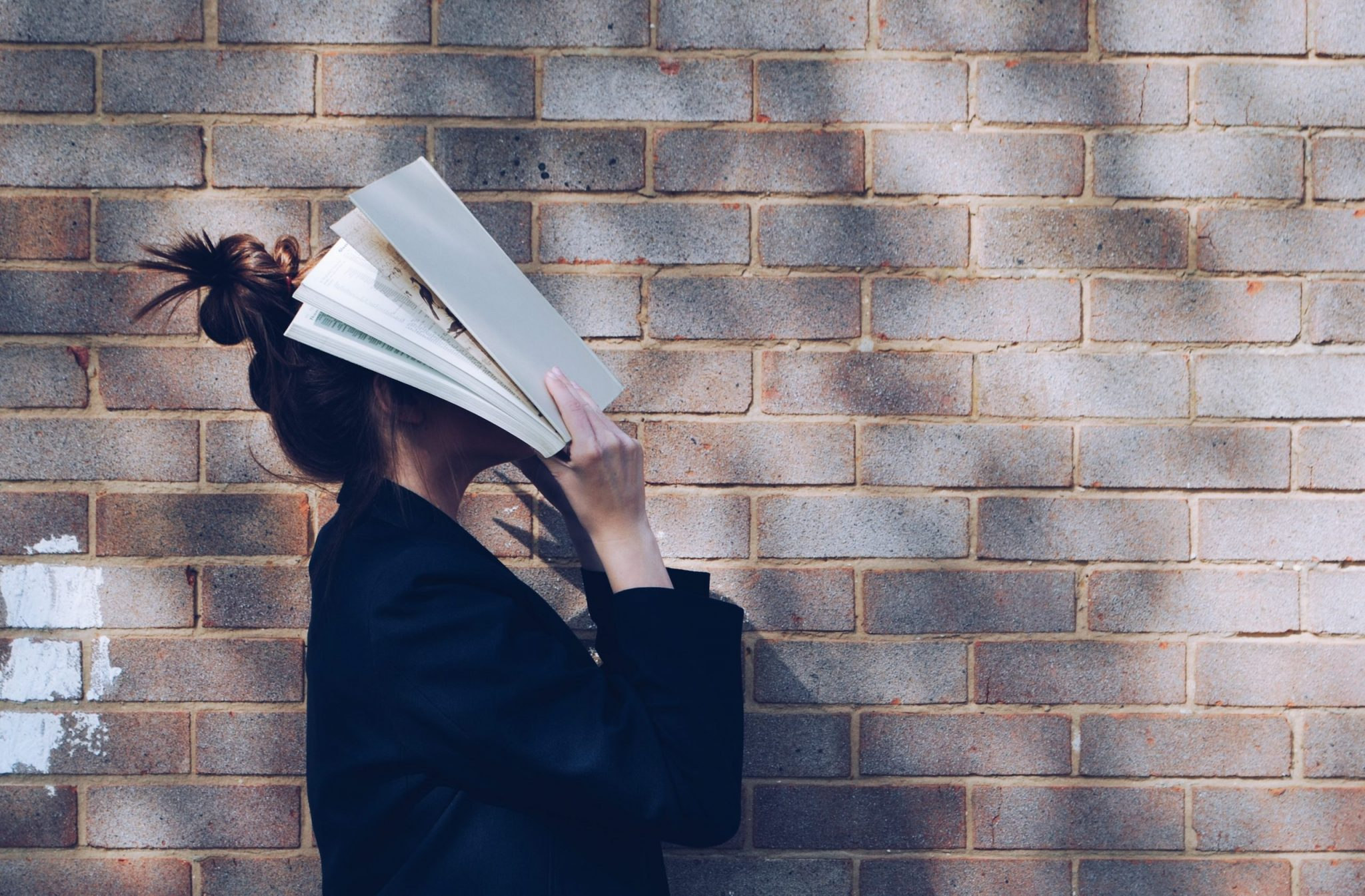 A photo of a woman with a book on her face.