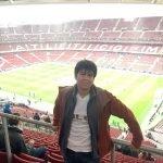 standing in front of a futbol stadium