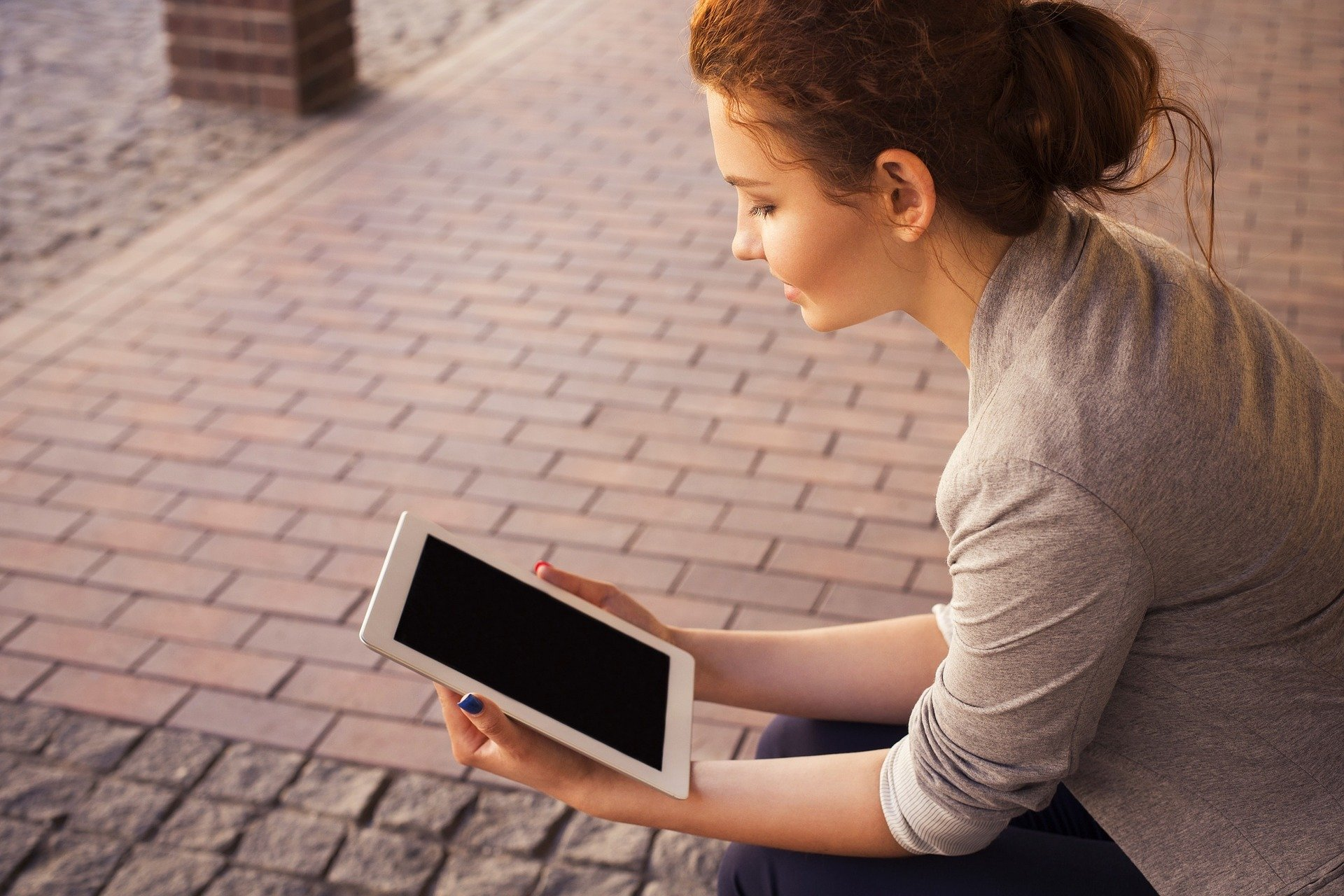 A photo of a woman looking at an iPad, which can be used for distance learning