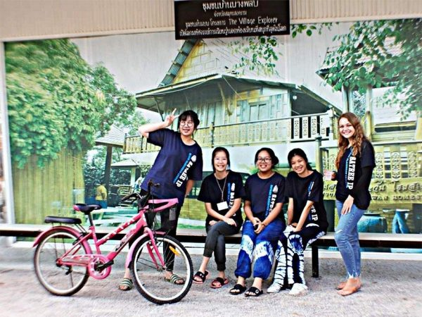 Students holding a bicycle in Thailand