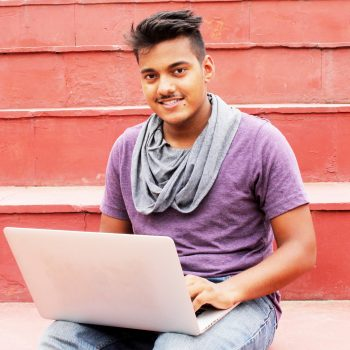 young man sitting outside with laptop